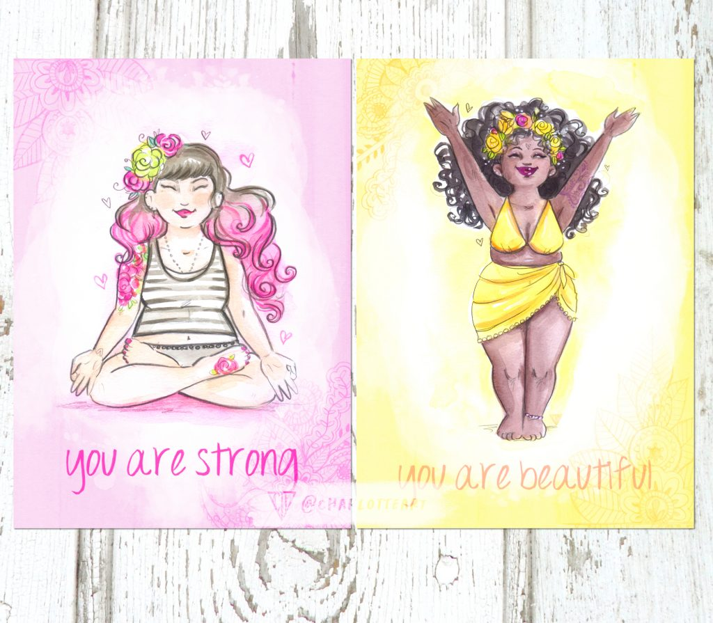 A photograph of two body acceptance yoga postcards one in pink and one in yellow. One says You are Strong, the other You are Beautiful.